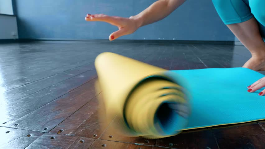 A woman unfolds a rug for practicing yoga in the studio.