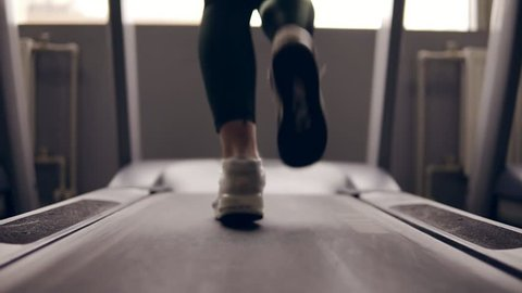 Slow motion footage of supposedly female legs in sneakers running on treadmill.