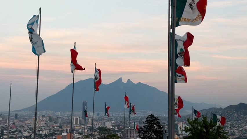 Historical Mexican flags blowing in the wind over Monterrey, Nuevo Leon, Mexico with Cerro de la Silla in the background.