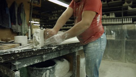 Worker made a part of gypsum cornice. Specialist separating ready part of cornice from gypsum at manufacture. Molding a cornice at manufactory.