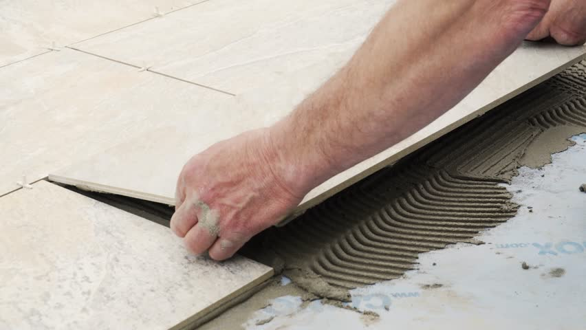 A man places a tile on the floor on top of cement. The tile is of mineral colors, like slate.