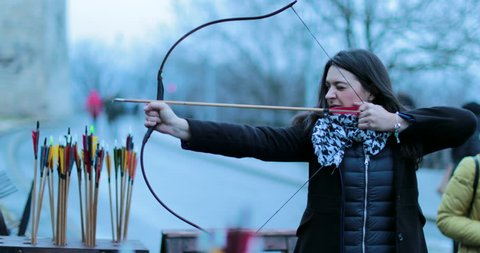 Woman archer shoots with a bow in 4K. Tourist woman practicing archery and smiles to camera. Woman focused on hitting target with arrow