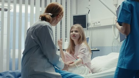 Cute Little Girl Sits on a Hospital Bed and Talks with Friendly Woman Doctor. Children's Hospital Pediatric Ward. Top Quality Health Care. Shot on RED EPIC-W 8K Helium Cinema Camera.