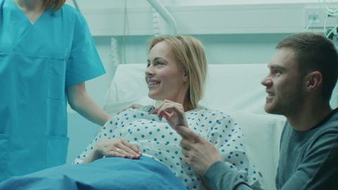 In the Hospital Midwife Gives Newborn Baby to a Mother to Hold, Supportive Father Lovingly Hugging Baby and Wife. Happy Family in the Modern Delivery Ward. Shot on RED EPIC-W 8K Helium Cinema Camera.