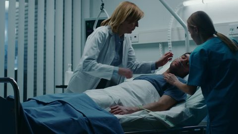 Emergency in the Hospital, Doctor and Nurse Rush into the Ward to Safe Dying Patient. Man is Lying on the Bed without Signs of Life. Doctors Do Everything to Resuscitate Him. Shot on RED EPIC-W 8K
