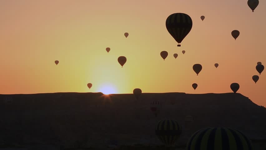 The balloon slowly flying in the sky at sunset, Cappadocia, Turkey