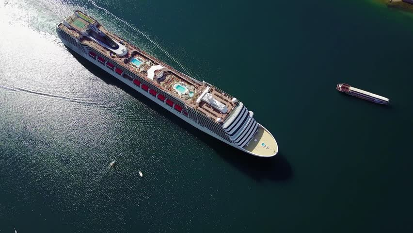 Aerial view of White luxury cruise ship docked in beautiful Caribbean sea close to the beach.