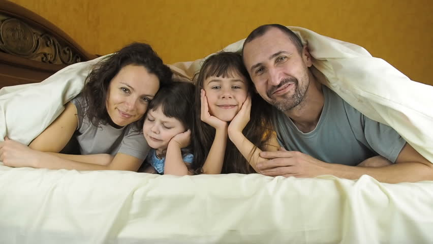 Family under the blanket. Happy family in the bedroom.