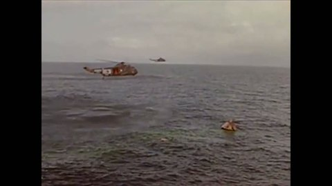 CIRCA 1960s - Divers recover the unmanned Apollo command module after a splashdown and it is brought aboard the USS Boxer, at sea, in 1966.