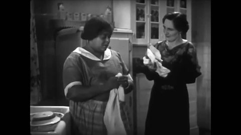 CIRCA 1930s - An African American maid gossips with the woman of the house, in a piece of romance fiction by Beatrice Burton Morgan, in 1935.