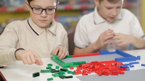 Two boys erect buildings from a children's plastic designer
