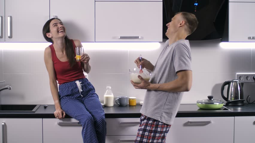 Beautiful couple of young adults cooking breakfast in the kitchen. Handsome man in pajamas dancing to entertain and make his girlfriend laugh. Smiling cheerful married couple having fun in the morning