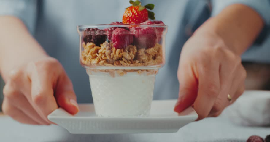 Closeup slow motion shot of woman bringing granola with yogurt to the table.