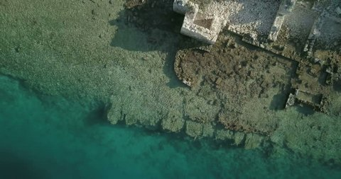 Rising bird's eye aerial drone footage with camera straight down ascending above clear turquoise water, harbor and ancient sunken city ruins of Kekova Island in Turkey. 4k at 23.97fps