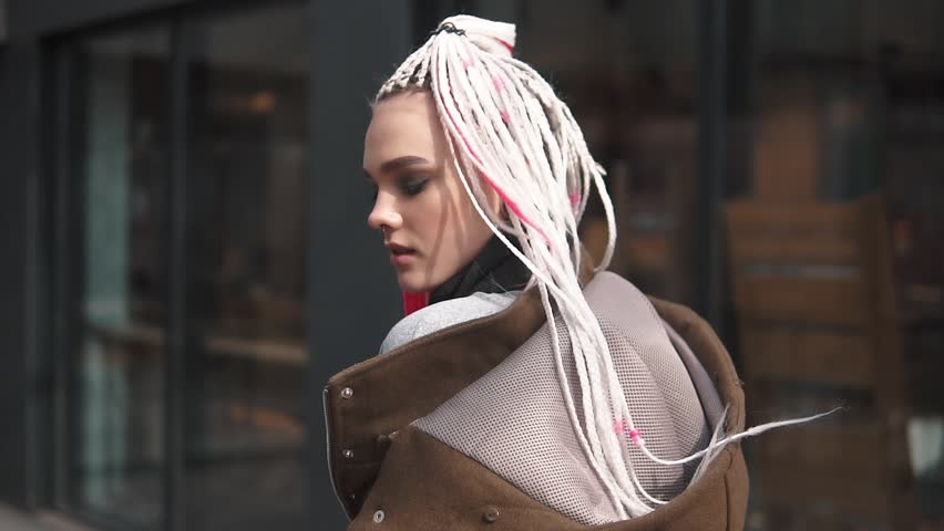 girl with an unusual appearance on the background of urban architecture. teenager with dreadlocks and piercing. a modern youth culture. back view. slow motion