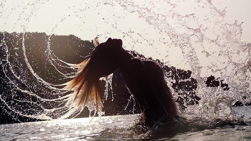Young woman in bikini splashes water tossing ocean water with her long hair over the sun during beautiful sunset. slow motion. 1920x1080 | Shutterstock HD Video #1009370471
