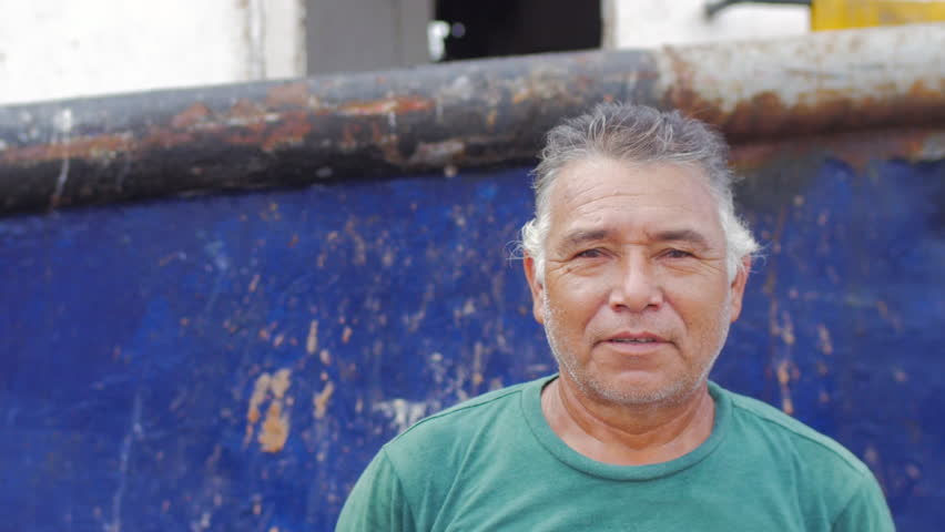 Close-up portrait of an older man of hispanic heritage smiling in front of a docked boat in Mexico | Shutterstock HD Video #1009371791