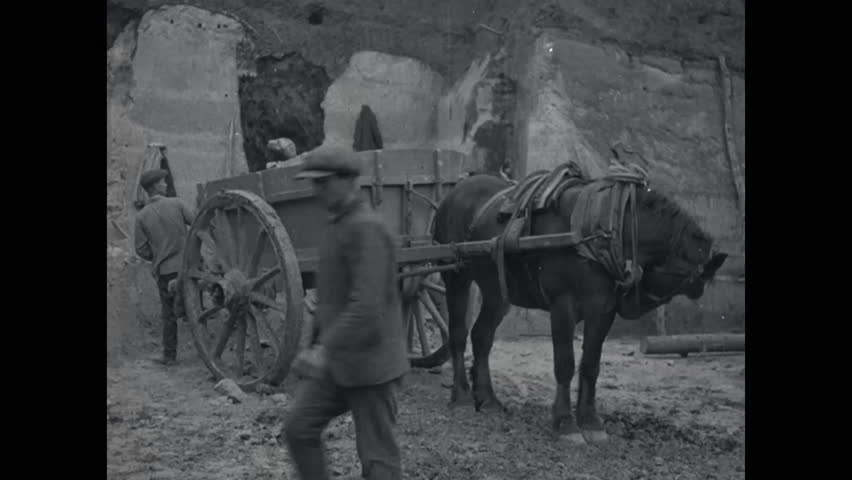 CIRCA 1919 - Quarry workers are shown filling a horse-drawn wagon and a farmer travels with a cart and poses with a dog in Limburg in the Netherlands.