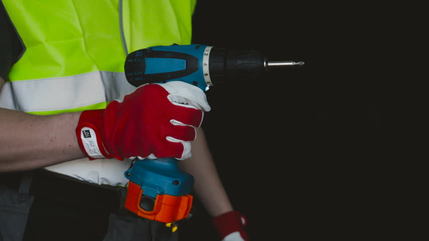 The builder or the repairman holds in his hand a screwdriver, a reflective vest, red gloves, a black background. | Shutterstock HD Video #1009385381