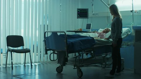Sick Little Child Lying in the Hospital Bed Sleeping, Her Mother Worries Sits on a Chair Beside, Hoping fore the Best. Dramatic Family Moment. Shot on RED EPIC-W 8K Helium Cinema Camera.