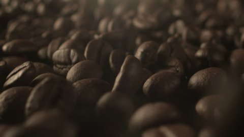An extreme close up shot of roasted coffee beans falling down against a dark background.