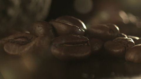 An extreme close up shot of roasted coffee beans getting crushed by a stone.