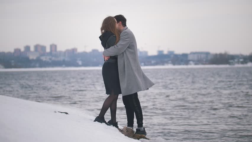 Happy young man and woman kissing on the riverside | Shutterstock HD Video #1009406111