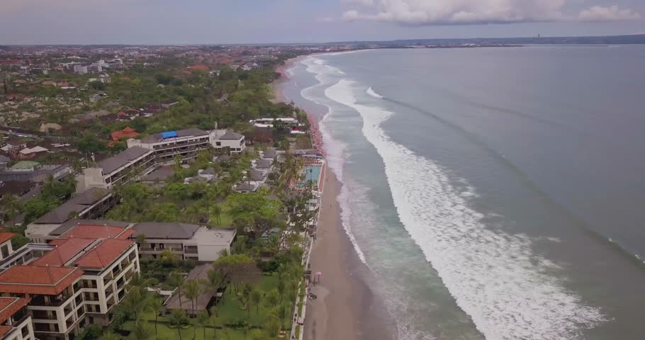 Seminyak beach drone 4k footage Bali with nice waves crashing against the sand closer to the water on a blue sunny day with lots of green trees