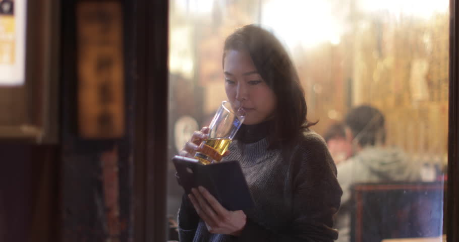 Japanese woman in restaurant drinking beer and looking out of window. Tokyo, Japan