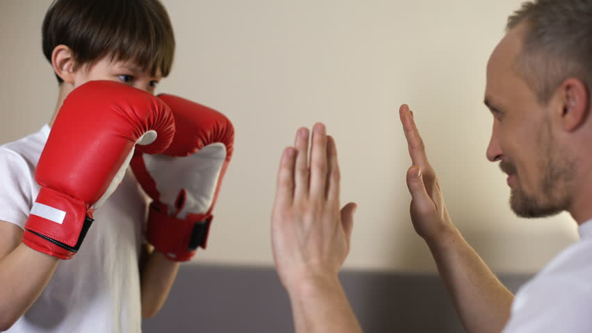 Cute kid practicing boxing punches with his coach, having fun with father, sport
