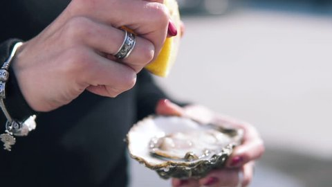 Close-up shot of women pouring lemon juice on the open oysters at the street. Delicious seafood in hand, Dynamic Slow motion