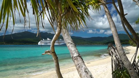 Tropical island beach with beautiful ocean and a cruise ship in the distance at Mystery Island in Vanuatu.
