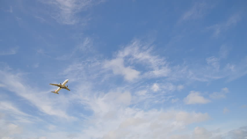 Time lapses of clouds and airplane take off against the blue sky