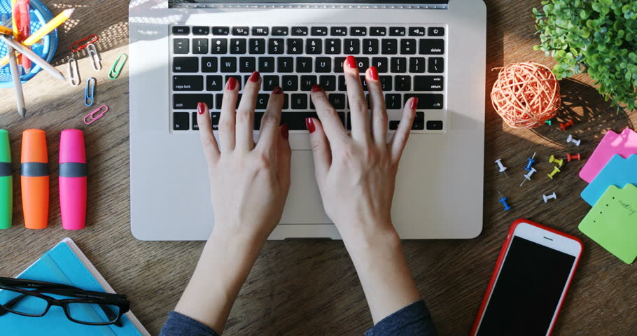 Woman hands using touchpad and typing on keyboard laptop close-up top view modern smartphone working art space desk internet searching online business creative innovation writing freelancer sunlight | Shutterstock HD Video #1009521791