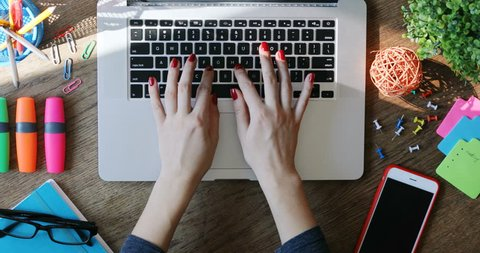 Woman hands using touchpad and typing on keyboard laptop close-up top view modern smartphone working art space desk internet searching online business creative innovation writing freelancer sunlight