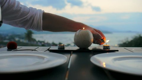 Male hand using lighter for candle lit on romantic dinner for two. Man lighting candle on dinner table on background sea landscape