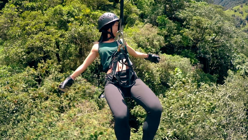 An Asian Tourist Sliding On A Zipline Over The Forest In The Mountain In Banos Ecuador