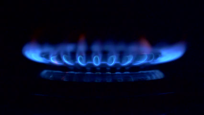 Gas is switching on, apearing blue flame. Gas stove on black background.