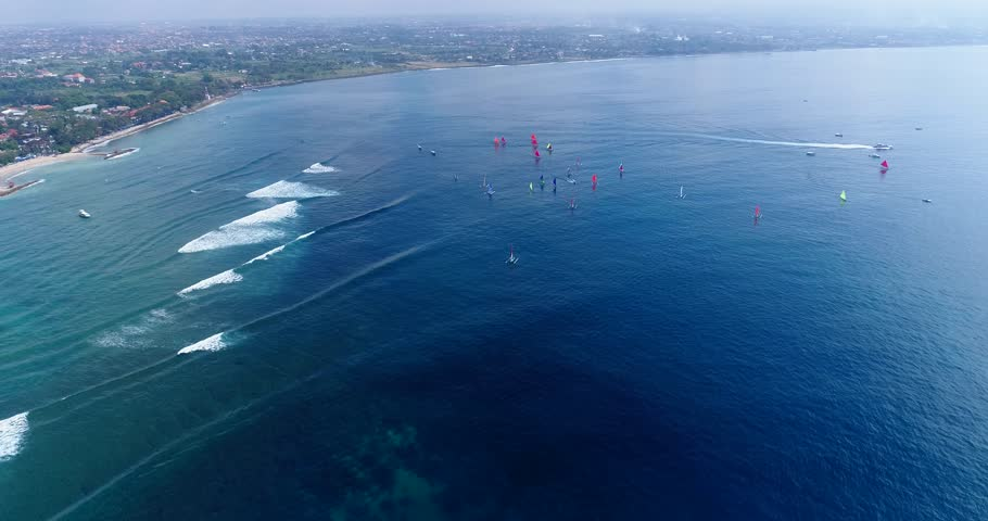 Drone footage of boats participating at a jukung race in Sanur, they are navigating along the beach with their colorful sails, waves are breaking on the shallow reef. The camera is going over the wate | Shutterstock HD Video #1009537391