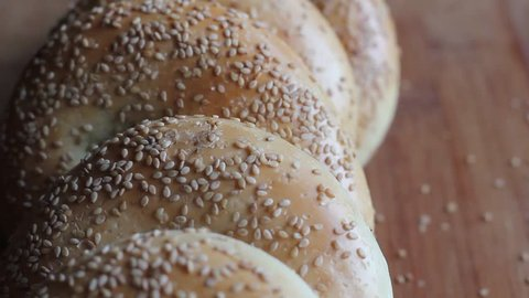 Pick a fresh bagel with sesame seeds on a wooden tray. HD video.