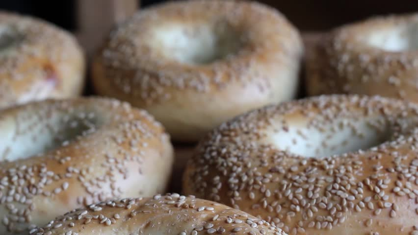 Fresh bagels with sesame seeds. Closeup in daylight. HD video.