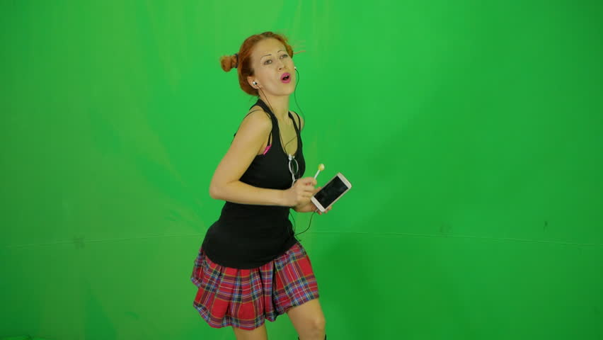 Schoolgirl with short plaid skirt and lollipop listing music by mobile phone and dancing at green-screen 50fps