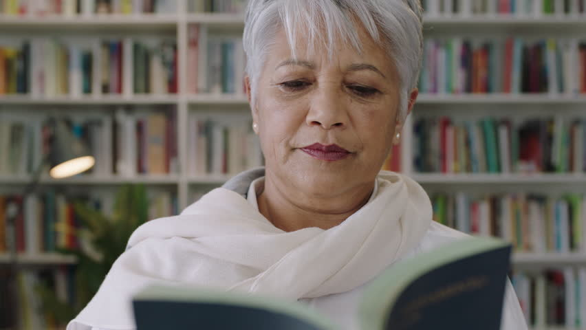 Portrait of friendly indian middle aged teacher standing in library reading book learning education | Shutterstock HD Video #1009563491