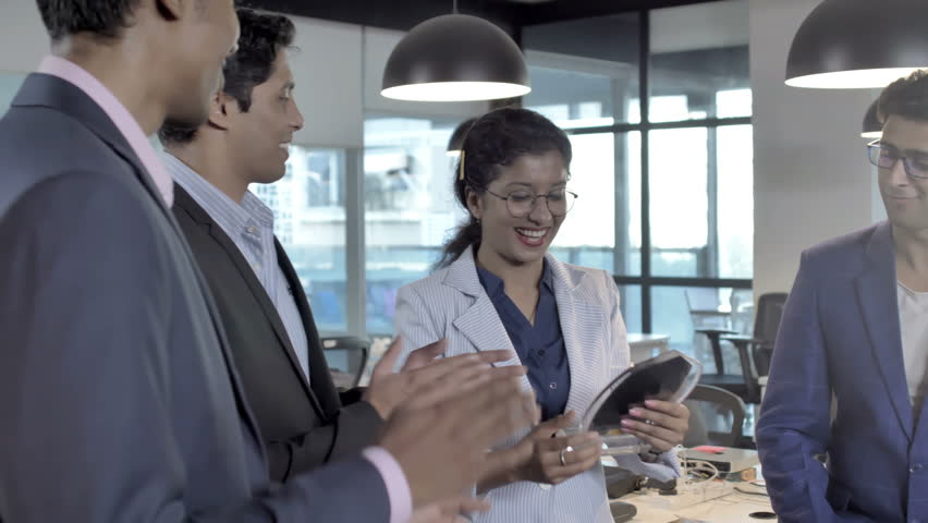 Mixed gender office colleagues smiling, applauding and congratulating a lady employee after winning an award. A group of male and female coworkers clapping and celebrating a success of a woman | Shutterstock HD Video #1009576811