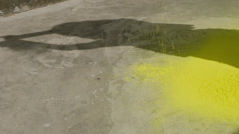 A slow motion clip of yellow colored powder falling on the ground.