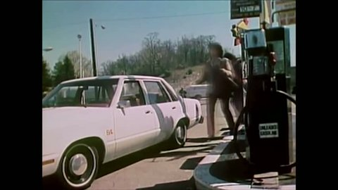 CIRCA 1981 - A gas station attendant is flummoxed by a woman's electric car, developed by NASA.