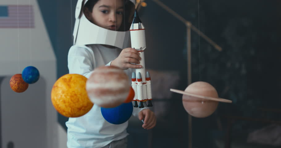CU Little kid boy wearing cardboard astronaut helmet launching a toy rocket from a spaceport through planets. 4K UHD 60 FPS SLOW MO
