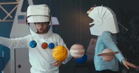 WIDE Cute little boy and girl siblings or friends wearing cardboard astronaut helmets flying toy rocket through planets, exploring deep space. 4K UHD 60 FPS SLOW MO