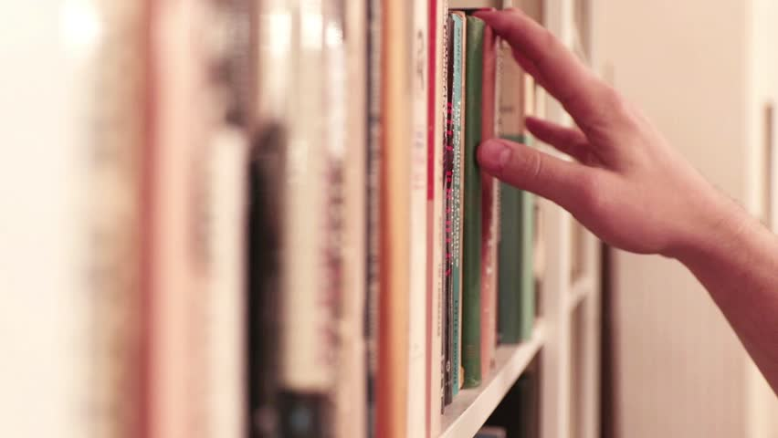 Hand reaches for and pulls classic book from library shelf; vintage look.