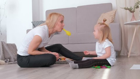 Attractive young blond mom inflate a balloon for her charming daughter sitting near the sofa. Family pastime.